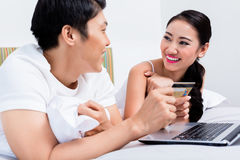 Chinese couple shopping online from their bedroom. Happy Chinese couple shopping online from their bedroom stock photography
