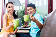Chinese couple surfing on sofa drinking coffee Royalty Free Stock Image