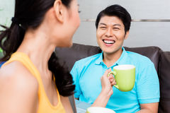Chinese couple surfing on sofa drinking coffee royalty free stock photos