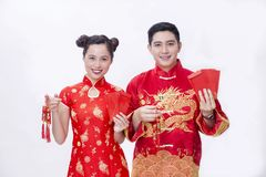 Chinese couple holding good luck item for new year. Chinese couple wear red to celebrate chinese new year smiling with the ang bao and hangings Royalty Free Stock Image