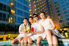Chinese couples drinking cocktails in hotel pool bar. Two young and handsome Asian Chinese couples or friends drinking cocktails in a luxurious and fancy hotel royalty free stock photo
