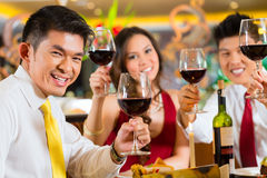 Chinese couples toasting with wine in restaurant. Two Asian Chinese Couples or friends or business people toasting during dinner or lunch in a elegant restaurant Stock Image