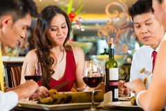 Chinese couples toasting with wine in restaurant royalty free stock photo