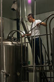 Chinese craft beer brewery. Brewmaster Wang Rui Geezer checking on his beer at his Chengdu Harvest Brewery Stock Photo
