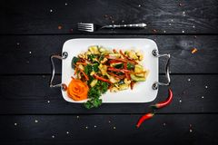 Chinese cucumber salad with cashews on the white plate. Chinese cucumber salad with cashews and cutlery on the white plate, black wooden background, top view Stock Photos
