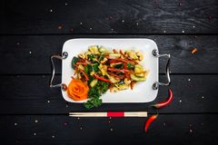 Chinese cucumber salad with cashews on the white plate. Chinese cucumber salad with cashews. Served chopsticks on the white plate, black wooden background, top Stock Image