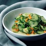 Chinese cucumber salad on the white plate Close up. Chinese cucumber salad on the white plate. Asian cuisine. Bell pepper, cucumber and sesame seeds. Vegetarian Royalty Free Stock Photos