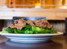 Chinese Cuisine: Beef with Rapini. Mongolian beef over green vegetable on white plate reflecting on dark brown wood table with picture taken from a front angle royalty free stock photo