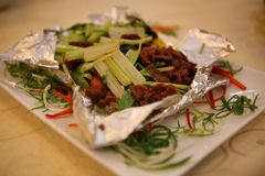 Chinese dish of beef, vegetables and celery, baked in foil and server on a white plate. royalty free stock photography