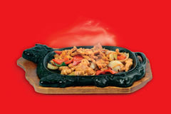 Chinese cuisine. Sizzling chicken. Chinese cuisine. Sizzling chicken on a red background Royalty Free Stock Photography