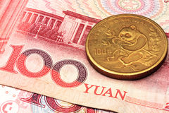 Chinese currency with gold coin. A chinese gold coin on a background of chinese money Royalty Free Stock Photo