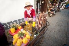 Chinese die vrouw bij een Riksja met fruit wordt geladen. Royalty-vrije Stock Fotografie