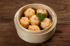 Chinese dim sum in a bamboo steamer box. Isolated on a wood table Stock Photos