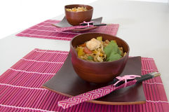 Chinese Dinner. Two sets of stir fry in bamboo bowls with chopsticks on pink place mats Stock Images