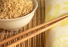 Chinese dinner closeup. A plate of raw rice and chopsticks on bamboo Royalty Free Stock Photo