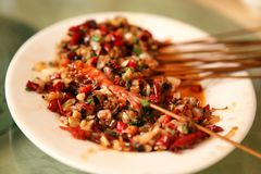 Chinese dish fried shrimps on skewers with red pepper sauce, served on a white plate. stock image