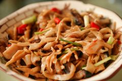 Chinese dish of meat, vegetables and chili peppers, served on a white plate. Beijing, China. royalty free stock photo