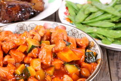 Chinese dishes. Chinese Sweet and Sour Pork Ribs Kung Pao Chickenon ,cooked snow peas,White Background Royalty Free Stock Image