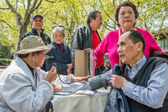 Chinese doctor ausculting people in fuxing park shanghai china Royalty Free Stock Photography