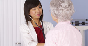 Chinese doctor listening to senior patient's heart Royalty Free Stock Photo