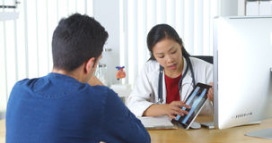 Chinese doctor reviewing xray with patient Royalty Free Stock Images