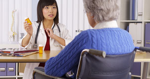 Chinese doctor talking about medication to elderly patient Stock Photos