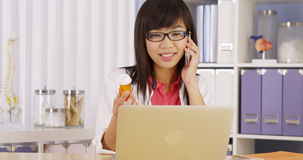 Chinese doctor talking on phone about prescription Royalty Free Stock Photography