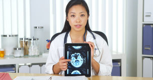 Chinese doctor talking to camera with tablet about xrays Stock Photography