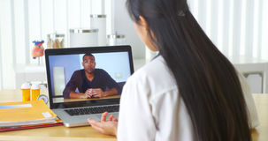 Chinese doctor video chatting with African patient stock image