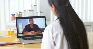 Chinese doctor video chatting with African patient Royalty Free Stock Photography