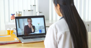Chinese doctor video chatting with elderly patient. In the office royalty free stock photo