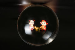 Chinese doll through glass spear. Cny on black background Stock Image