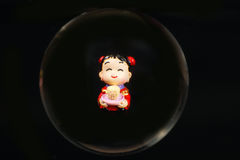 Chinese doll through glass spear. Cny on black background Royalty Free Stock Images