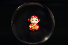 Chinese doll through glass spear. Cny on black background Royalty Free Stock Photo