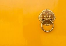 Chinese door handle put on the right. Golden chinese door handle put on the right of yellow door Stock Image