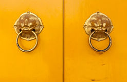 Chinese door handles on yellow doors. Golden chinese door handles on yellow doors in horizontal Royalty Free Stock Photos