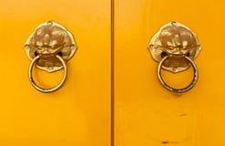Chinese door handles on yellow doors Royalty Free Stock Photos