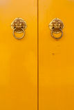 Chinese door handles on yellow doors vertical. Golden chinese door handles on yellow doors in vertical Royalty Free Stock Image