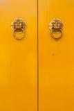 Chinese door handles on yellow doors vertical Royalty Free Stock Image
