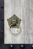 Chinese Door Knocker. A traditional Chinese brass lion knocker on a wooden door Royalty Free Stock Photo