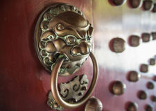Chinese Door Knocker. A door knocker is an item of door that allows people outside a place to alert those inside to their presence stock photography