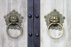 Chinese Door Knockers. Traditional Chinese brass lion knockers on a wooden door Royalty Free Stock Photo