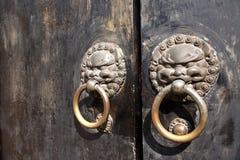 Chinese door knockers. Metal chinese door knockers with weathered wooden doors Stock Image