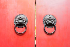 Chinese door knockers on a red gate Stock Photo