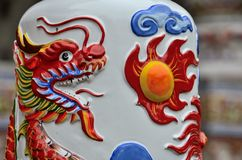 Chinese dragon breathes fire on ceramic art at temple Hat Yai Thailand. Hat Yai, Thailand - December 23, 2015: A royal Thai Chinese dragon breathes a ball of Royalty Free Stock Images