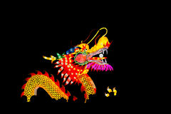 Chinese dragon in the crowd. Colorful chinese dragon on a black background in the silhouette of a crowd of people during a festivity royalty free stock images