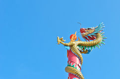 Chinese dragon wrap on pole with red ball in blue. Chinese dragon statue wrap on pole with red ball in blue sky Royalty Free Stock Photography