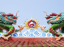 Chinese dragons. A pair of chinese dragons is  playing fired ball on a roof Stock Photos