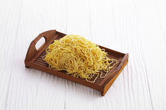 Chinese dry noodle in wooden dish. On white background Stock Photos