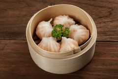 Chinese dumpling in a bamboo steamer box. Isolated on a wood table Royalty Free Stock Images